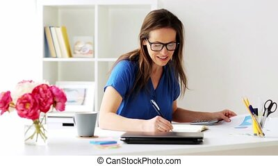 woman with calculator and notebook at office