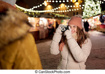 woman with camera photographing man at christmas