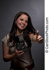 woman with camera posing thumbs up