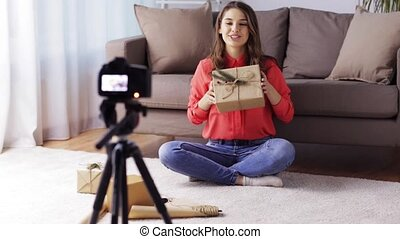 woman with camera recording video at home