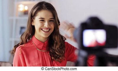 blogging, technology, videoblog, mass media and people concept - happy smiling woman or blogger with camera recording video and waving hand at home