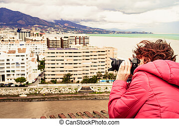 Woman with camera take photo in Fuengirola city, Spain