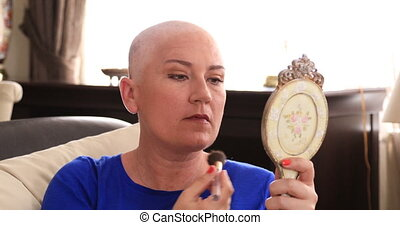 Woman with cancer applying make up - Portrait of a happy...