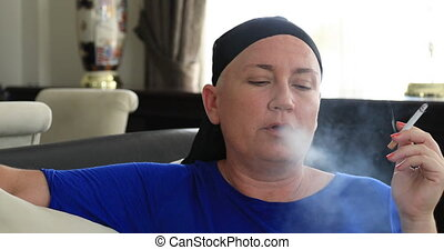 Woman with cancer smoking cigarette - Middle aged sick, bald...