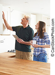Woman With Carpenter Inspecting New Fitted Kitchen
