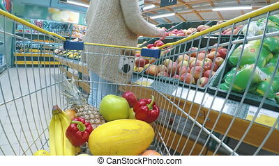 Woman with cart or trolley buying fresh vegetables and fruits at supermarket