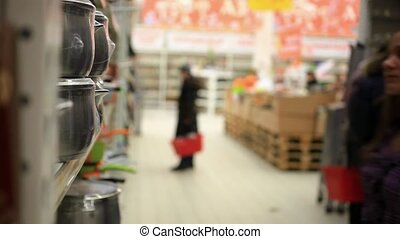 Woman with cart shopping buys a pan in supermarket at...