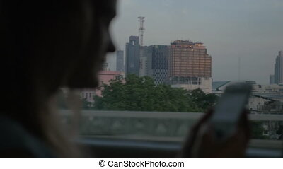 Woman with cell going by bus in Bangkok, Thailand
