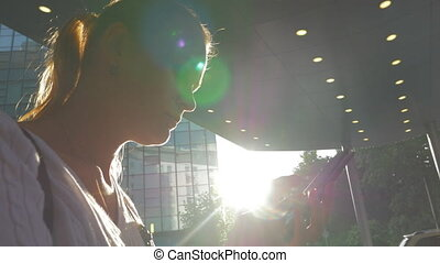 Woman with cell in city against bright sunshine