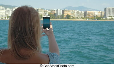 Woman with cell shooting sea and city from ship