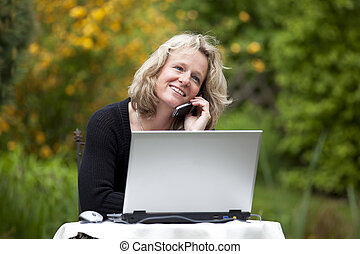 woman with cellphone and laptop