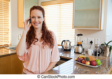 Woman with cellphone behind the kitchen counter