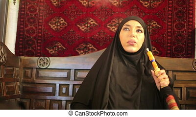 Woman with chador headscarf smoking shisha and drinking...