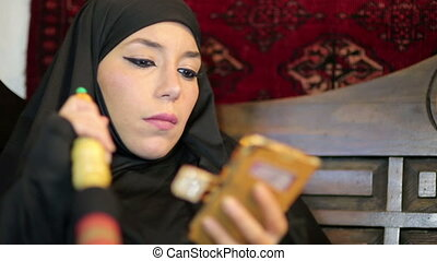 Woman with chador headscarf smoking shisha and using mobile...