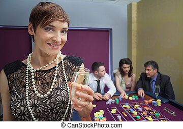 Woman with champagne at roulette table