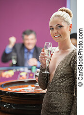 Woman with champagne standing beside roulette wheel