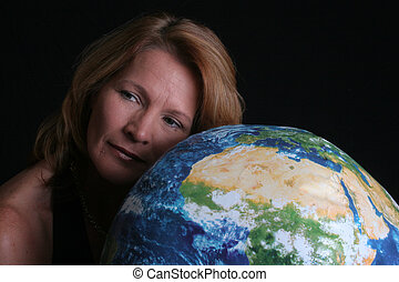 A pretty woman is lovingly laying her cheek on a globe of the world.