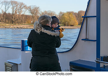 Woman with child in arm on a ship