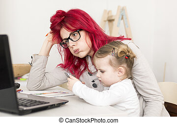 Woman with Child on Lap Looking Exhausted Infront of Computer