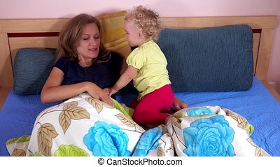 Woman with child play under wrap in bed
