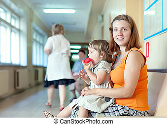woman with child with urinalysis sample