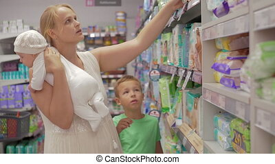 Woman with children buying diapers in the supermarket