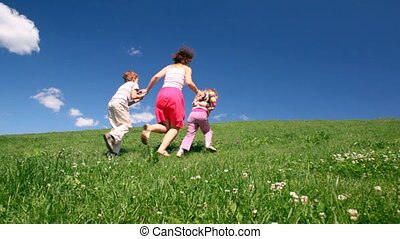 Woman with children holding hands rise on hill