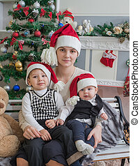 woman with children on the background of the Christmas tree