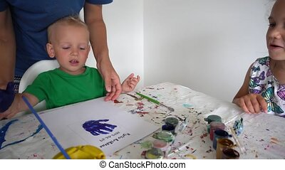 Woman with children paint hand palm print on paper with gouache. Gimbal motion