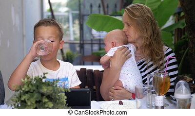 Woman with children relaxing in street cafe