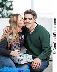 Woman With Christmas Gifts Kissing Man On Cheek