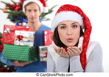 Woman with Christmas hat blowing kiss