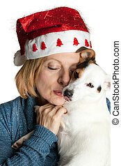 Woman with christmas hat hugging her jack russell.