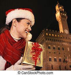 woman with Christmas present box looking into distance, Florence