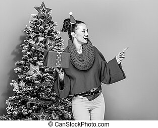 woman with Christmas present box pointing at something