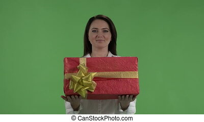 Woman with Christmas presents against green screen.