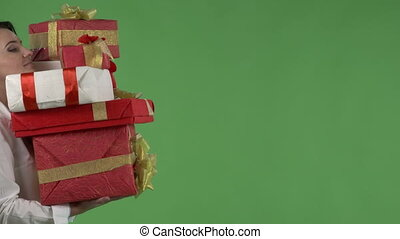 Business woman carrying pile of red white gift boxes against green screen
