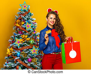 woman with Christmas shopping bag showing credit card -...