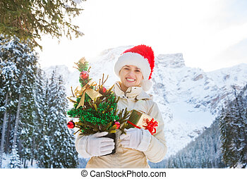 Woman with Christmas tree and gift box in the front of...