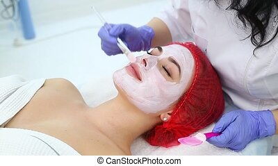 Woman with clay facial mask in beauty spa. - Cosmetician...