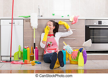 Woman with cleaning equipment and products on kitchen floor...