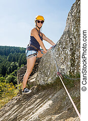 Woman With Climbing Equipment Standing On Rock