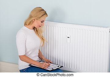 Woman With Clipboard Checking Digital Thermostat - Young...