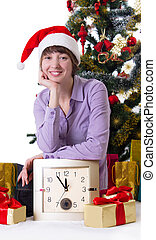 Woman with clock under Christmas tree