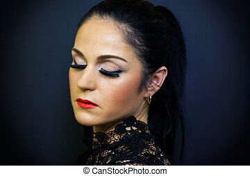 Woman with close eyes on dark background