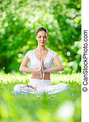 Woman with closed eyes in asana position prayer gesturing