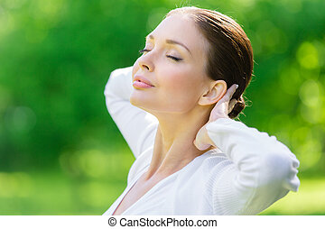 Woman with closed eyes puts hands behind head
