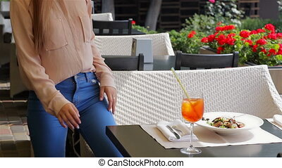 Woman with cocktail at the terrace of cafe