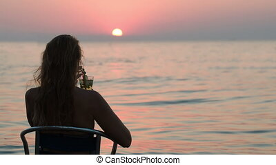 Woman with cocktail enjoying sunset on the shore