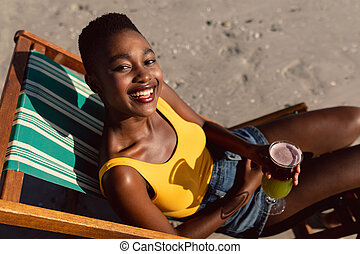 Woman with cocktail glass relaxing in a beach chair on the beach